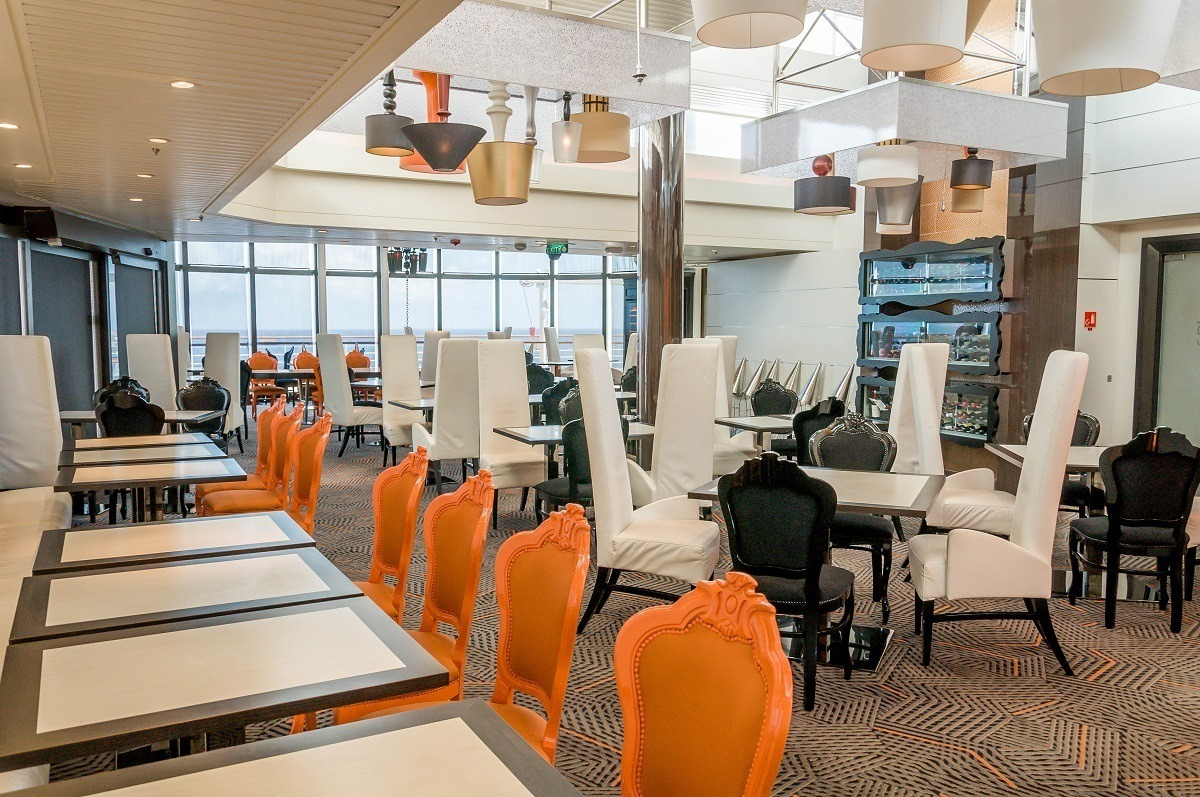 Orange, white, and black chairs at tables in the empty Qsine Restaurant
