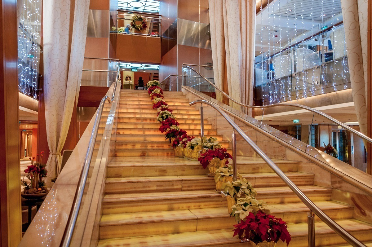 The main staircase of the Celebrity Summit lined with poinsettias