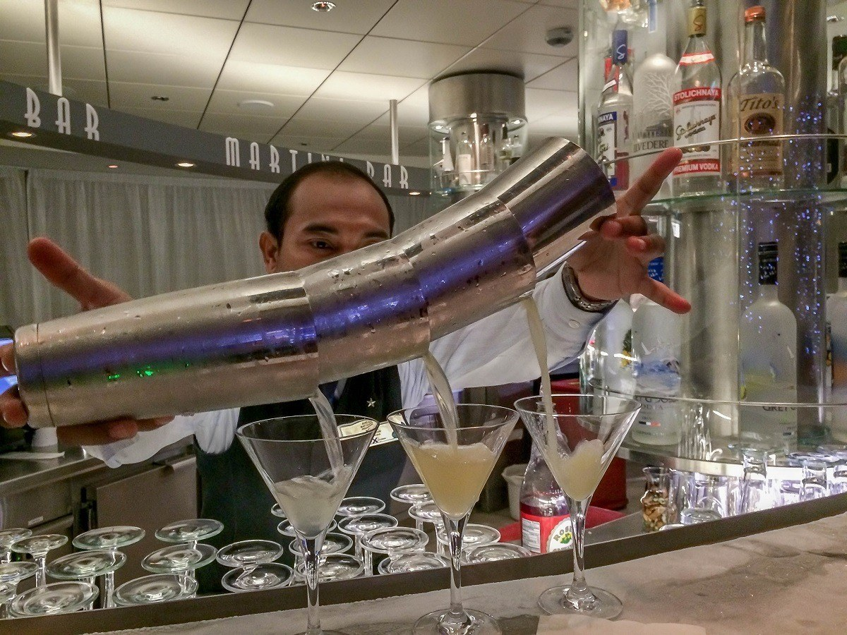 Bartender pouring three martinis at once