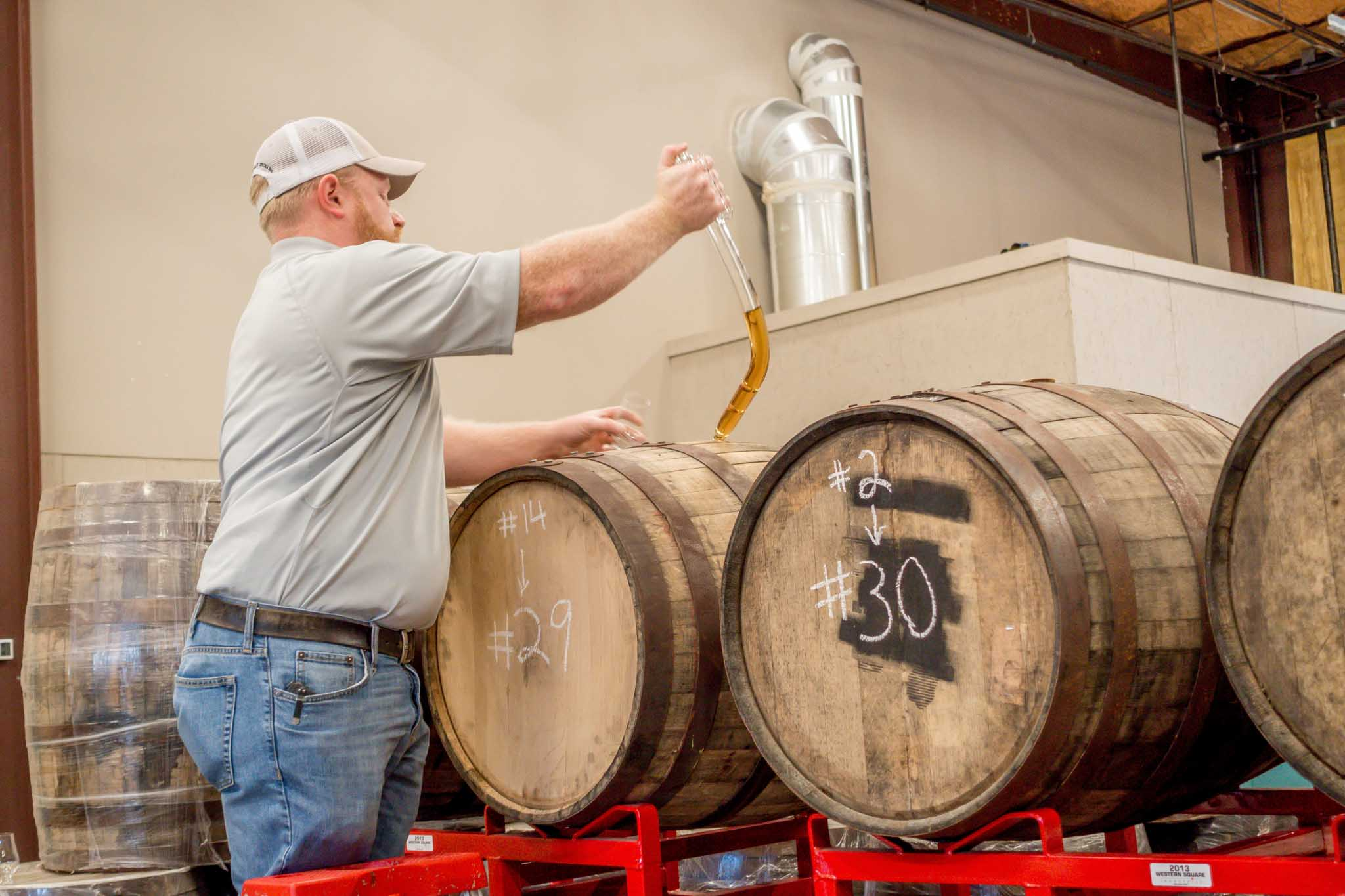 Opening a barrrel of whiskey at Ironroot Republic, one of the distilleries in Texas