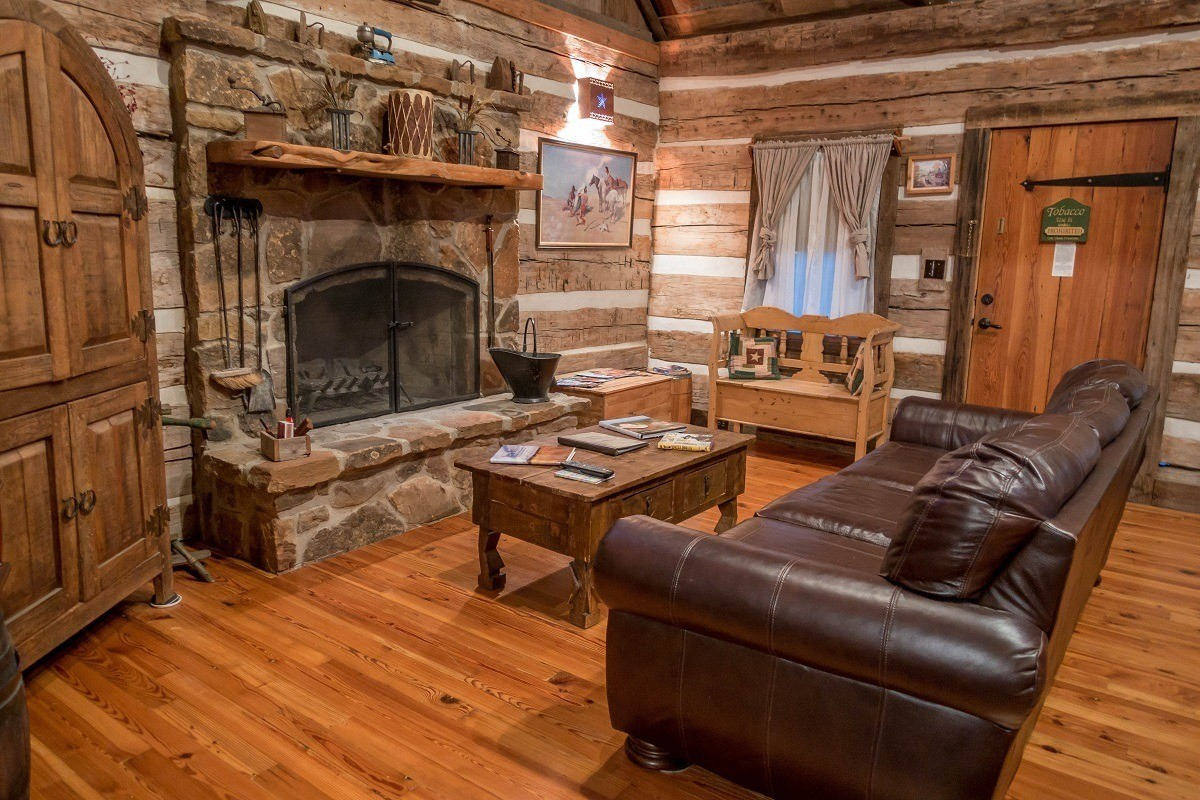 Living room of cabin with couch and fireplace at Cotton Gin Village