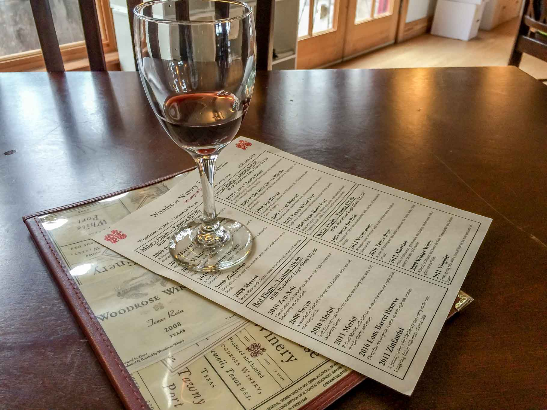 Wine glass and tasting menu at Woodrose Winery in Stonewall, Texas
