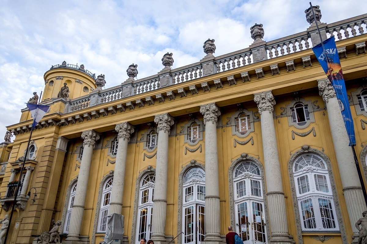 The white columns and yellow building of Szechenyi, one of the Budapest baths