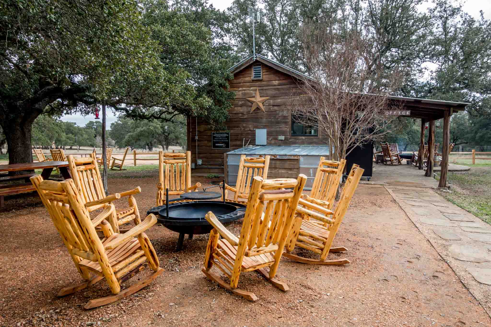 Rocking chairs and fire pits outside builing at Garrison Brothers Distillery