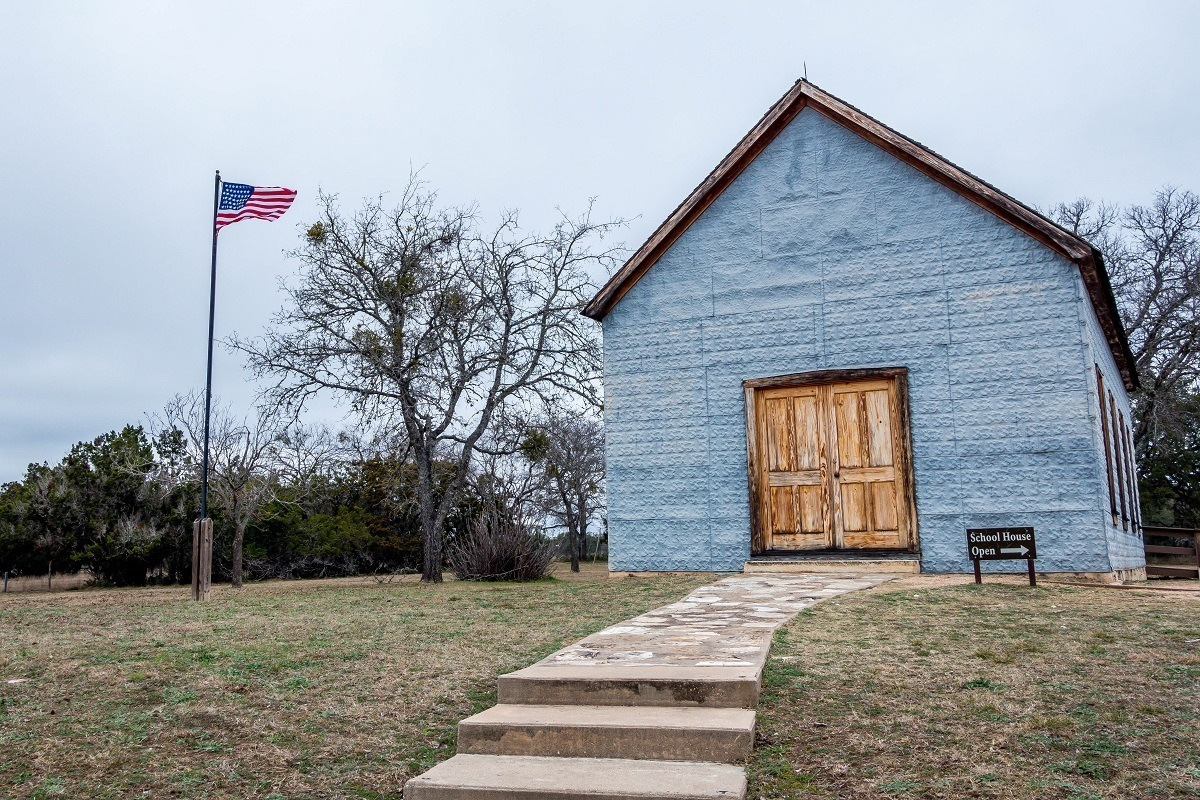 One-room school house alongside American flag at LBJ State Park