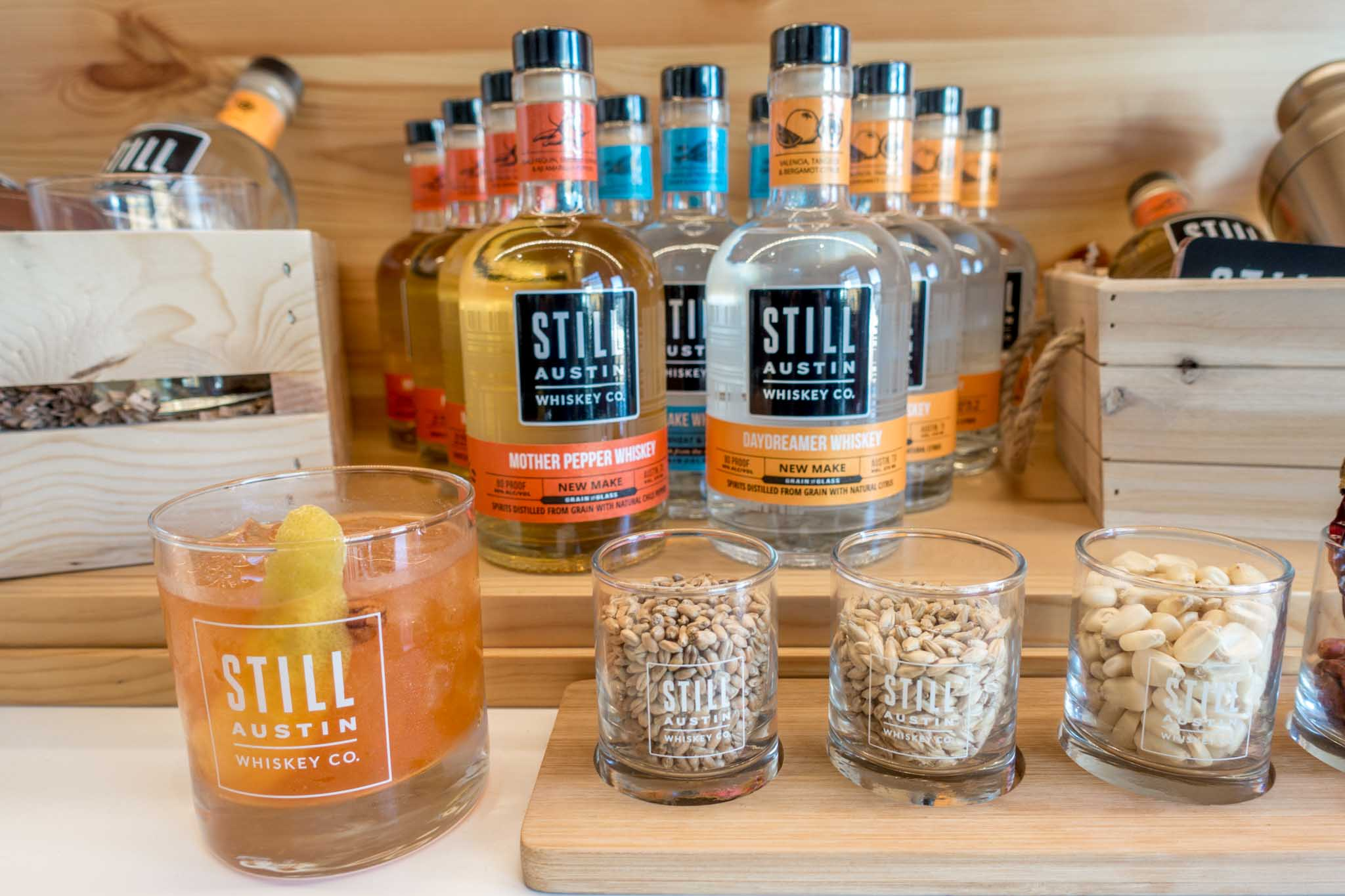Bottles and cocktail glass labeled as Still Austin Whiskey Co.