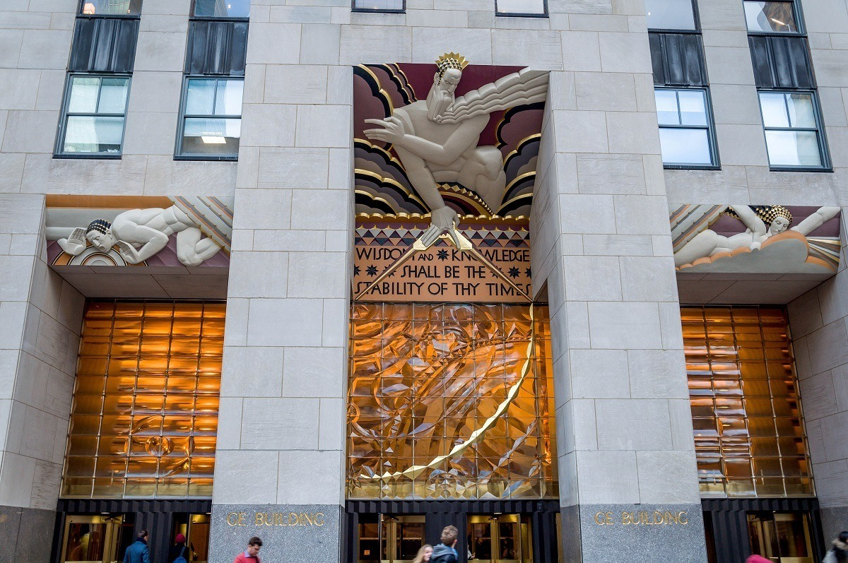 Gold, red, and white Art Deco relief Wisdom above door at Rockefeller Center