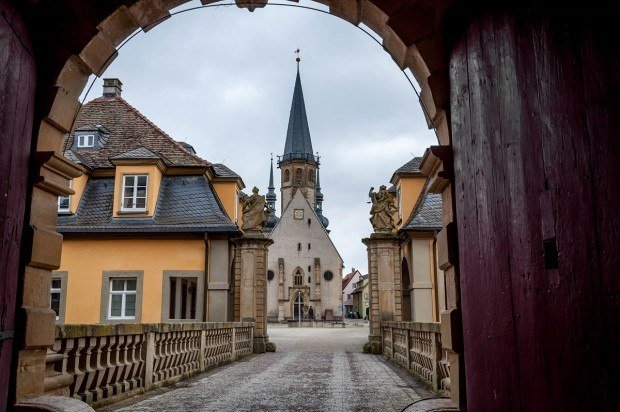 The gate and church in Weikersheim on a Romantic Road trip. The Romantic Road Germany itinerary leads from Wurzburg to Fussen and visits the best towns in Germany along the way.