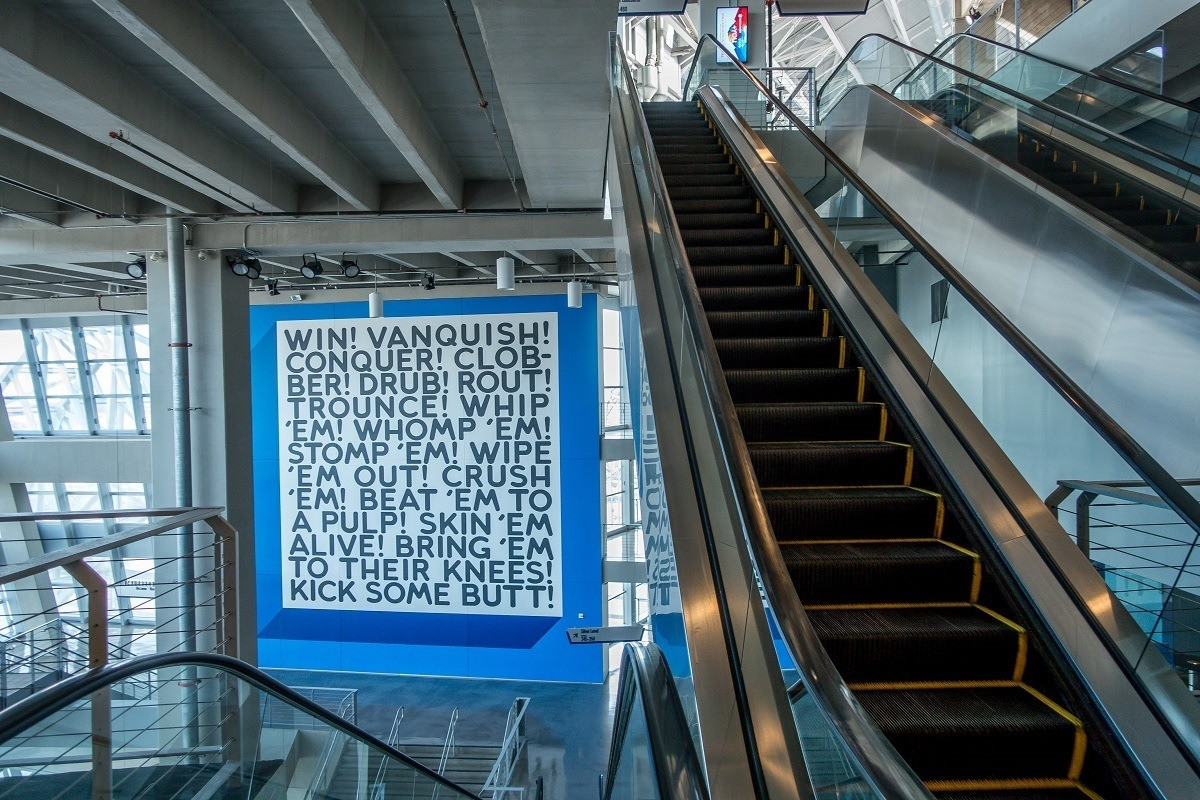 Word-based artwork hanging near escalators