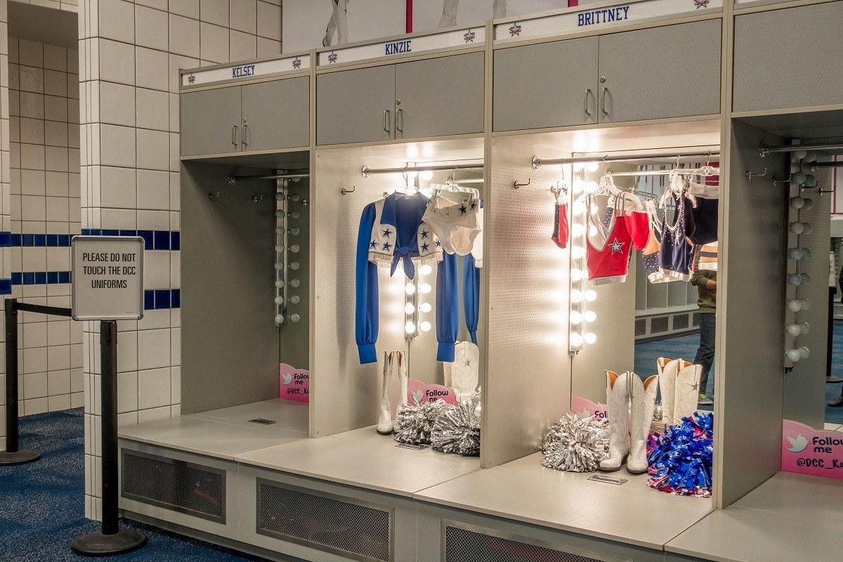 Cheerleaders' uniforms displayed in locker room on a stadium tour