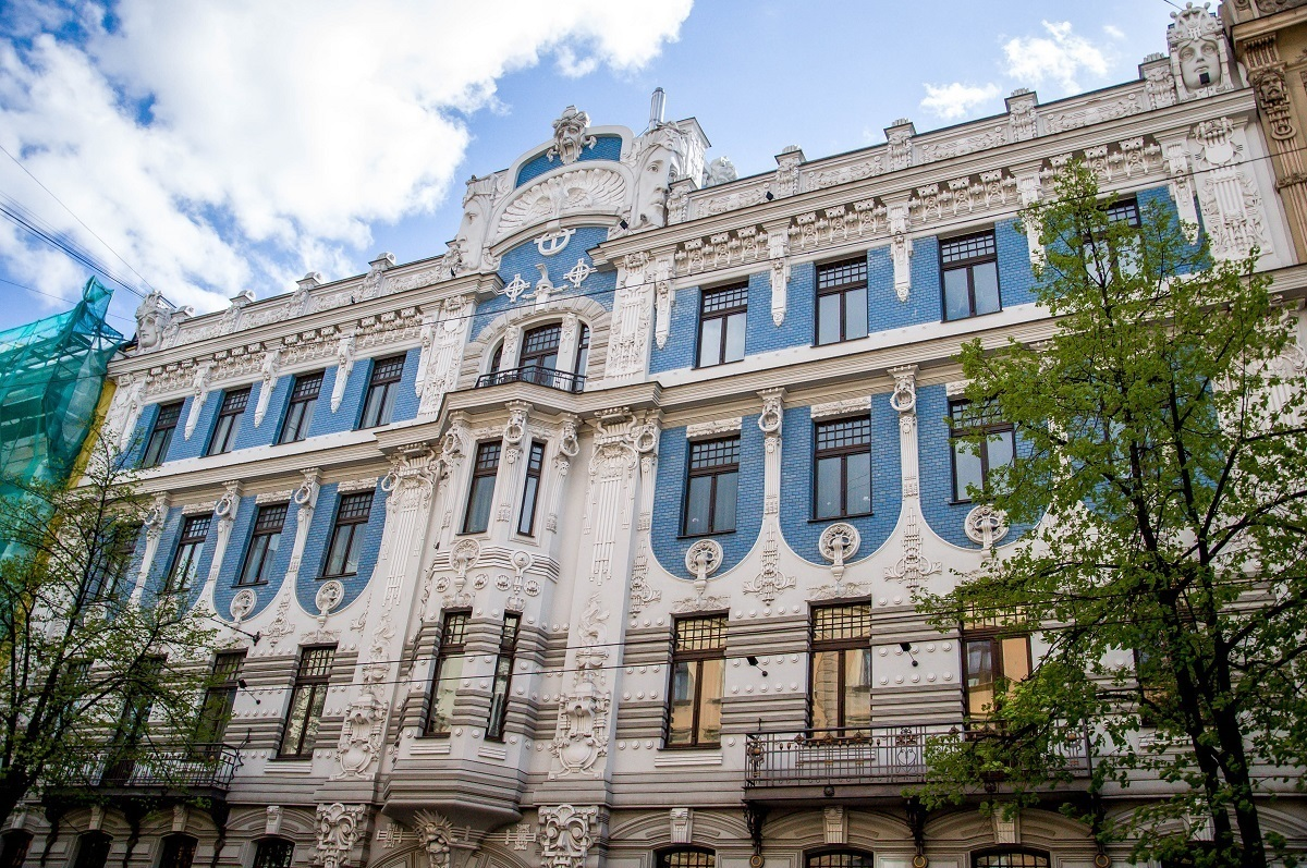 Blue and white building in Riga with carved faces designed by Mikhail Eisenstein