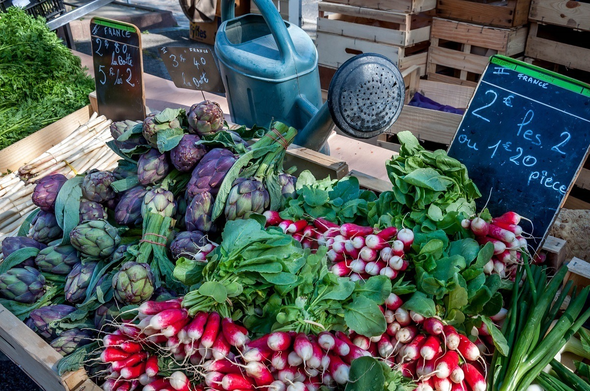 Radishes and artichokes at a Provence market in Arles France
