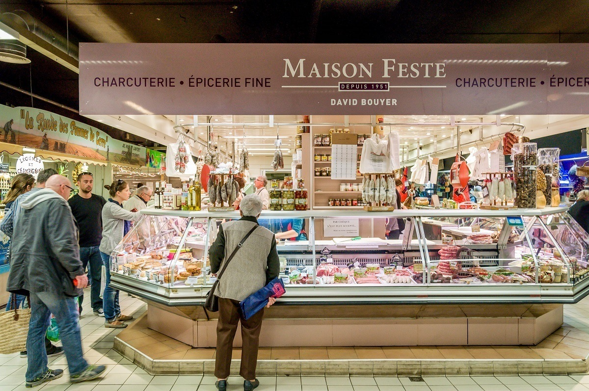 Charcuterie stall and people shopping at Les Halles