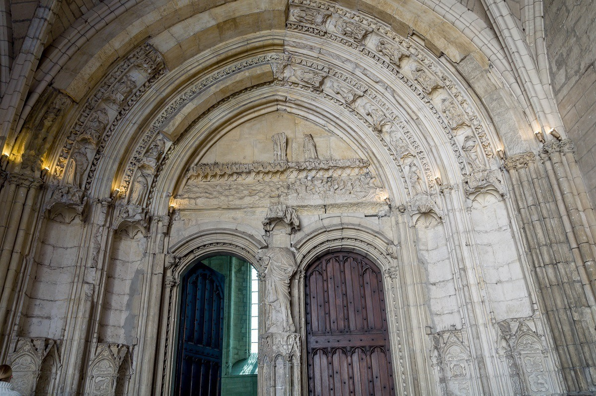 Arched stone entryway with carvings and wooden doors