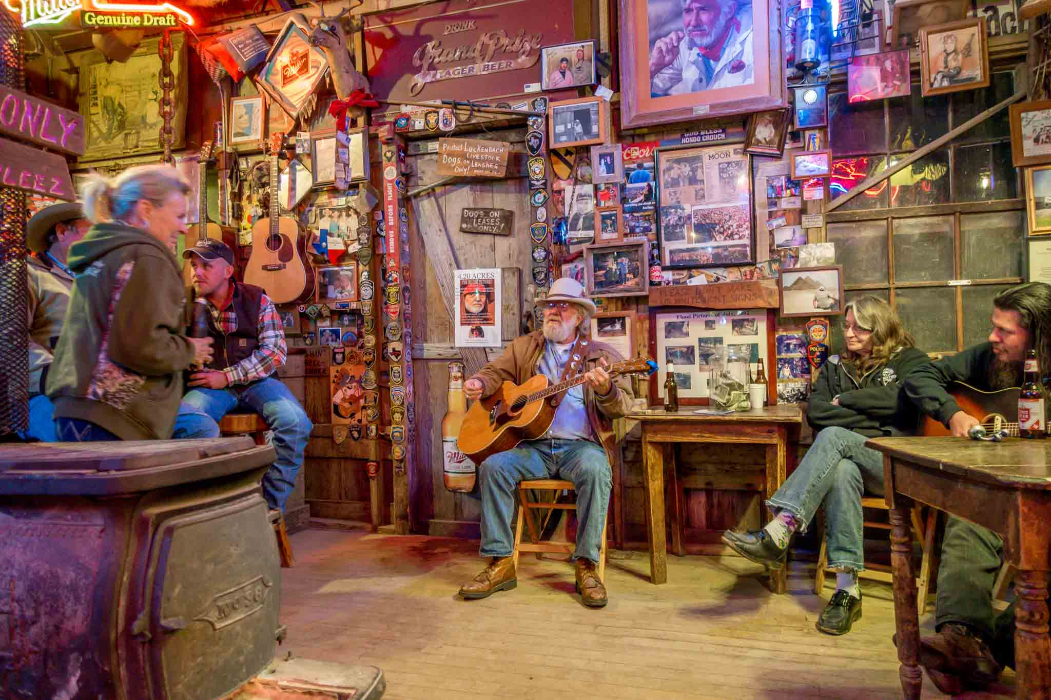 People listening to man playing guitar at Luckenbach