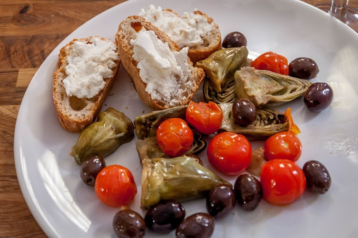 Artichokes Provencal with baguette and goat cheese on plate