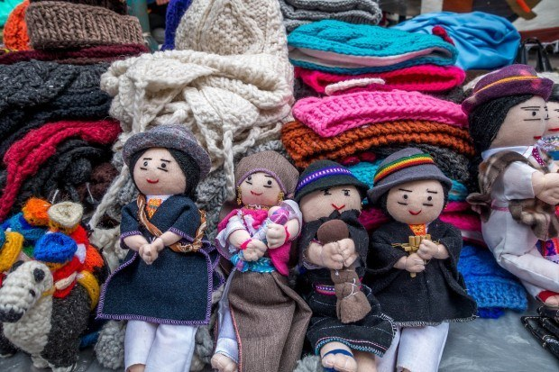Souvenirs like wool knit hats and dolls are available in the Otavalo market.