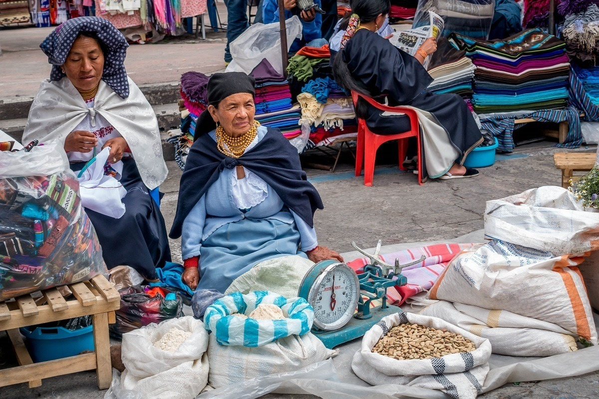 Women traditional dress selling beans and lentils in Otavalo's main square, called Plaza de los Ponchos.