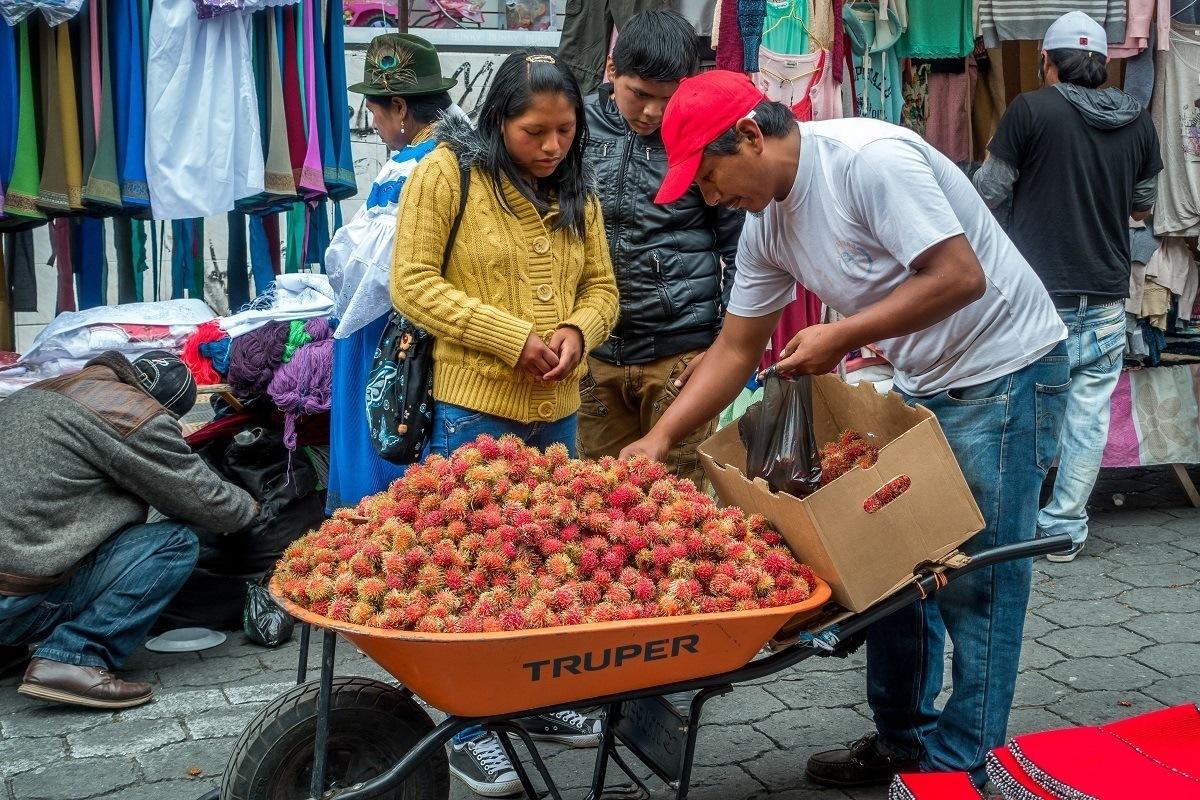 Vendor selling fruit in the Otavalo market.