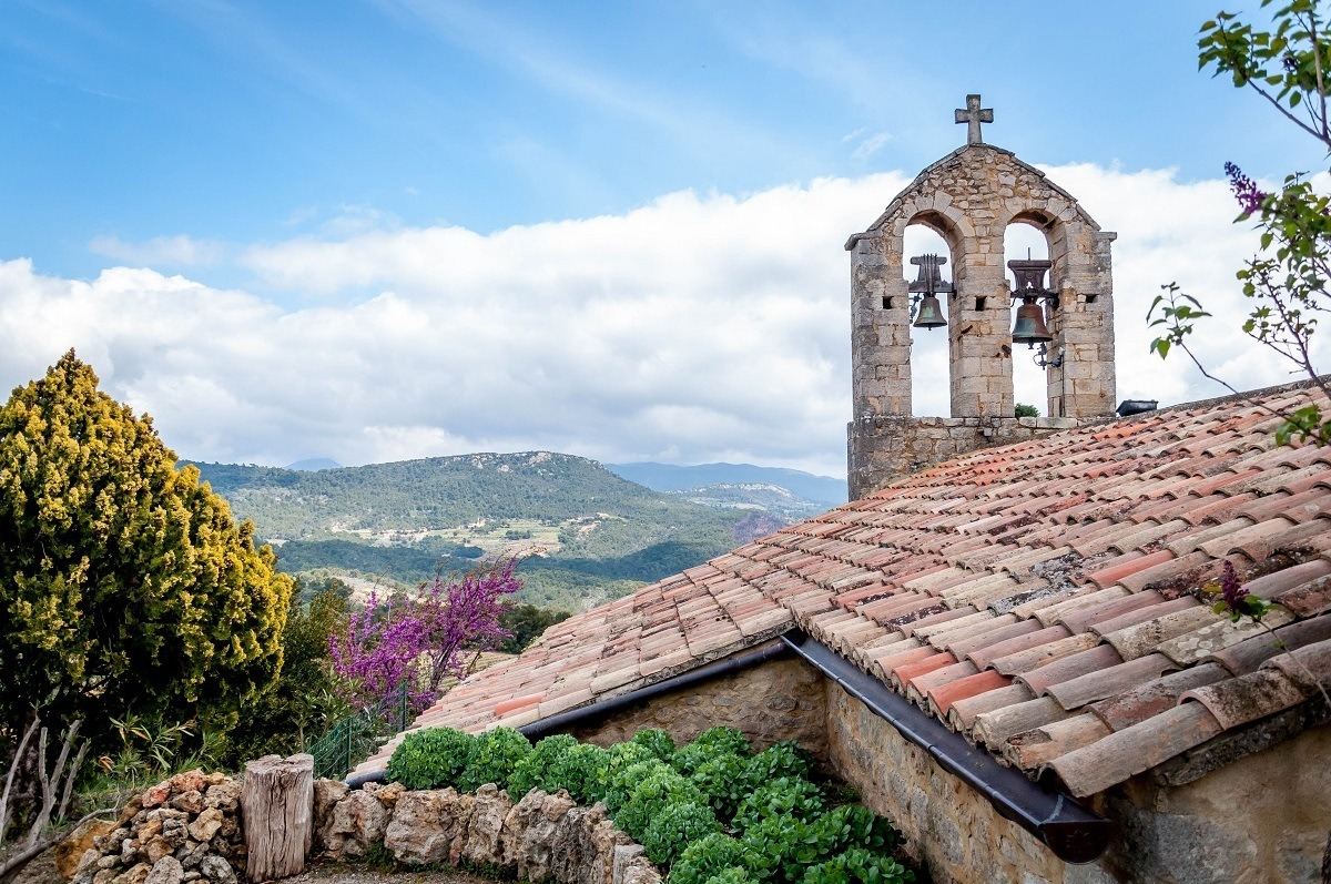 Church bells and tiled roof  overlooking a hilly landscape
