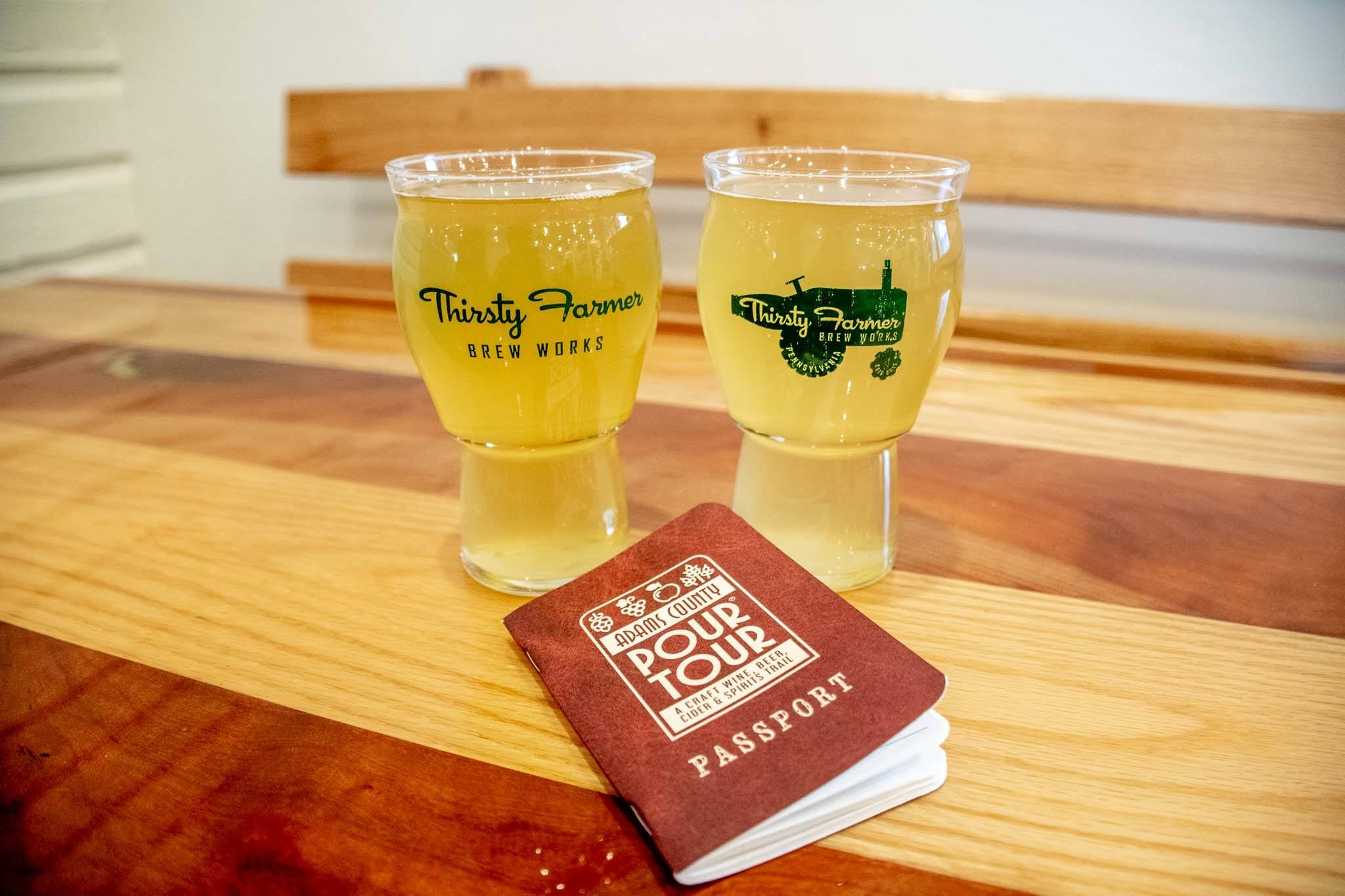 """Two full beer pint glasses and a """"Pour Tour"""" booklet on a wooden table at the Thirsty Farmer"""