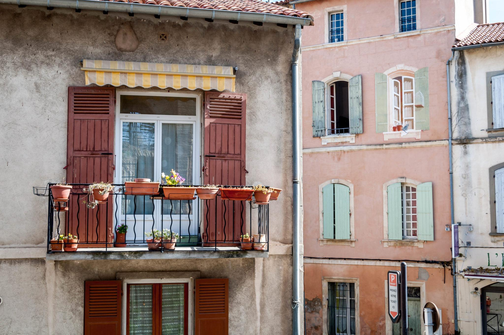 Window boxes and colorful window shutters in Arles, France