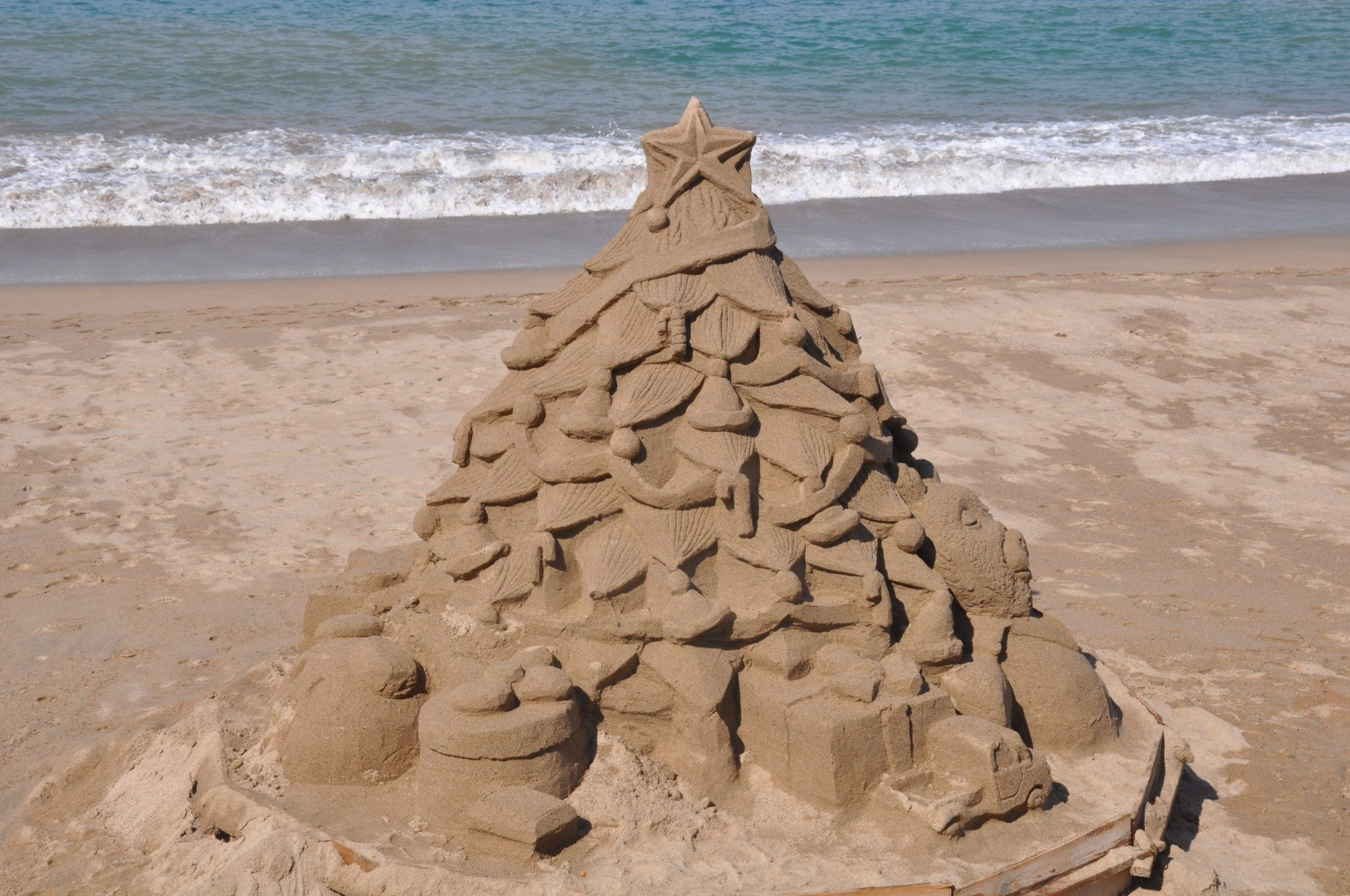 Sand sculpture of a Christmas tree on the beach in Mexico
