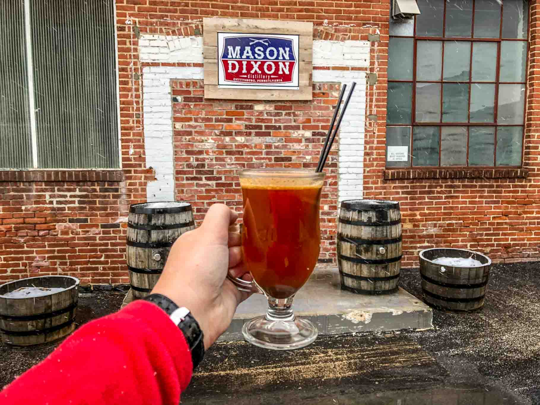 Cocktail in front of sign for Mason Dixon Distillery in Gettysburg PA