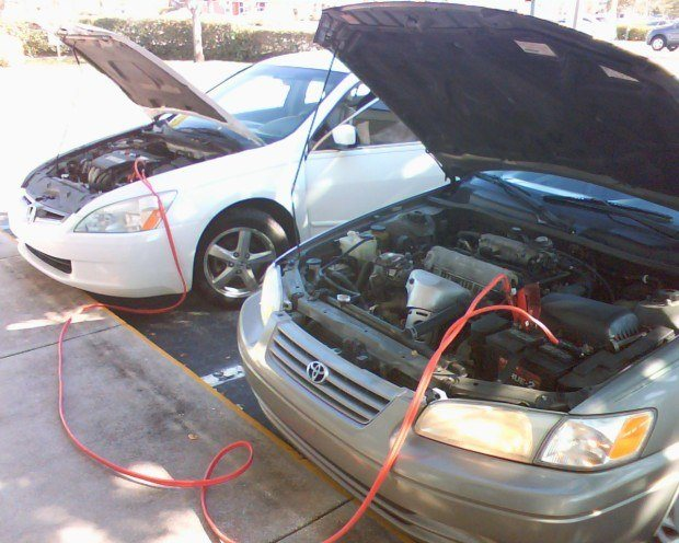 Using jumper cables to do an emergency start start of a car. They are an important item to have in your roadside emergency kit.
