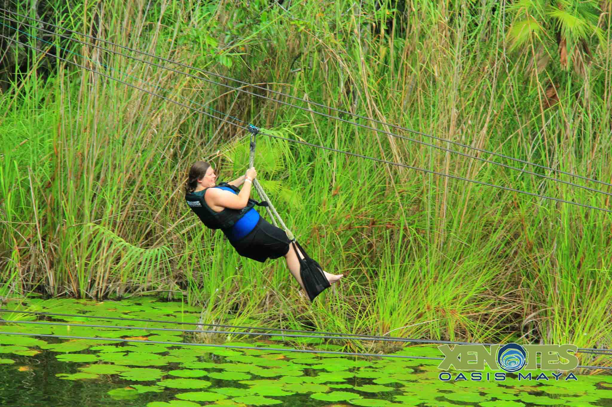 Woman zip lining into the water over lily pads