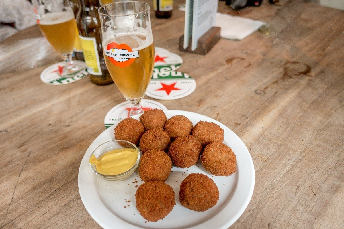 Bitterballen with mustard on a plate and a pint of beer