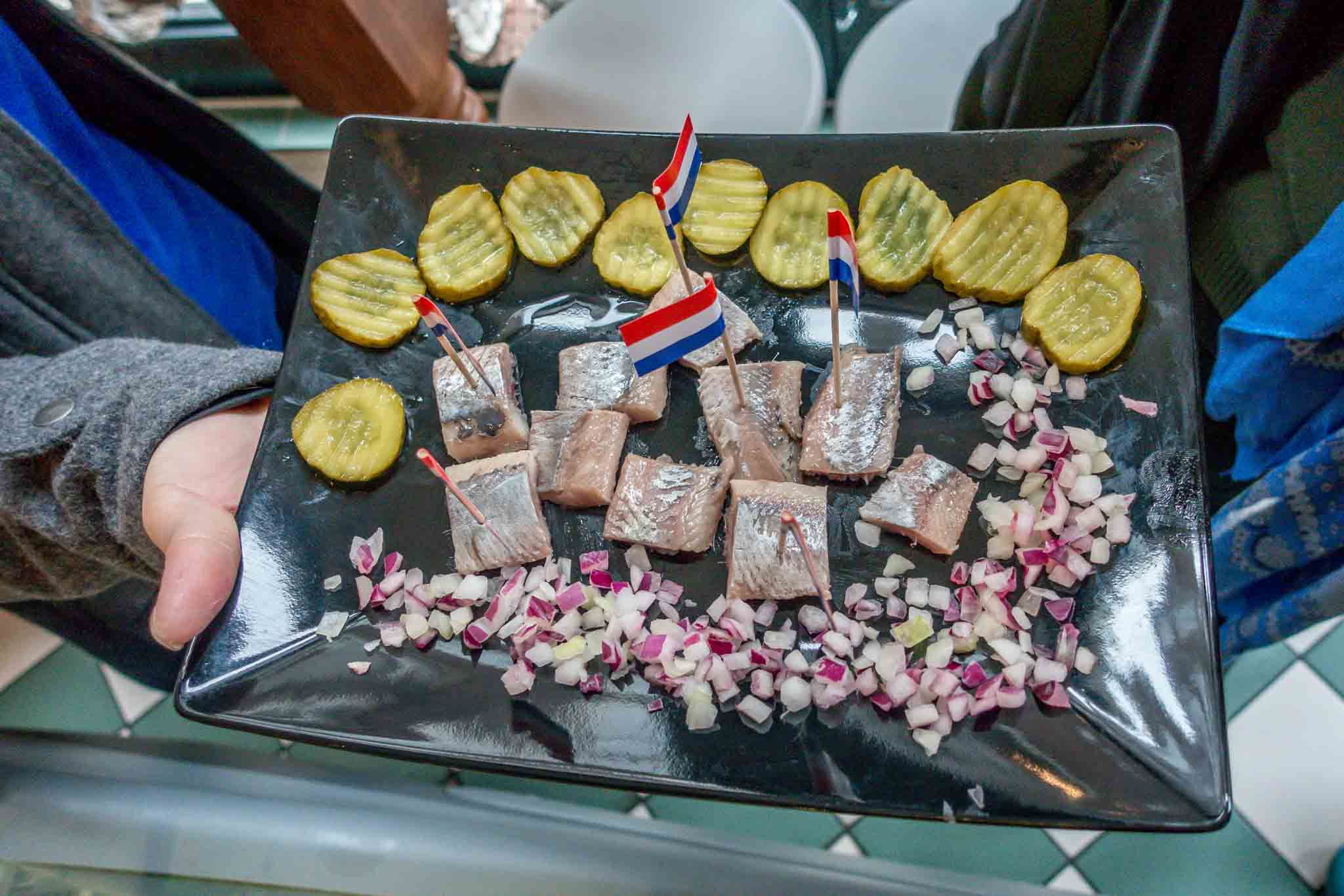 Platter of pickled herring, red onion, and pickles