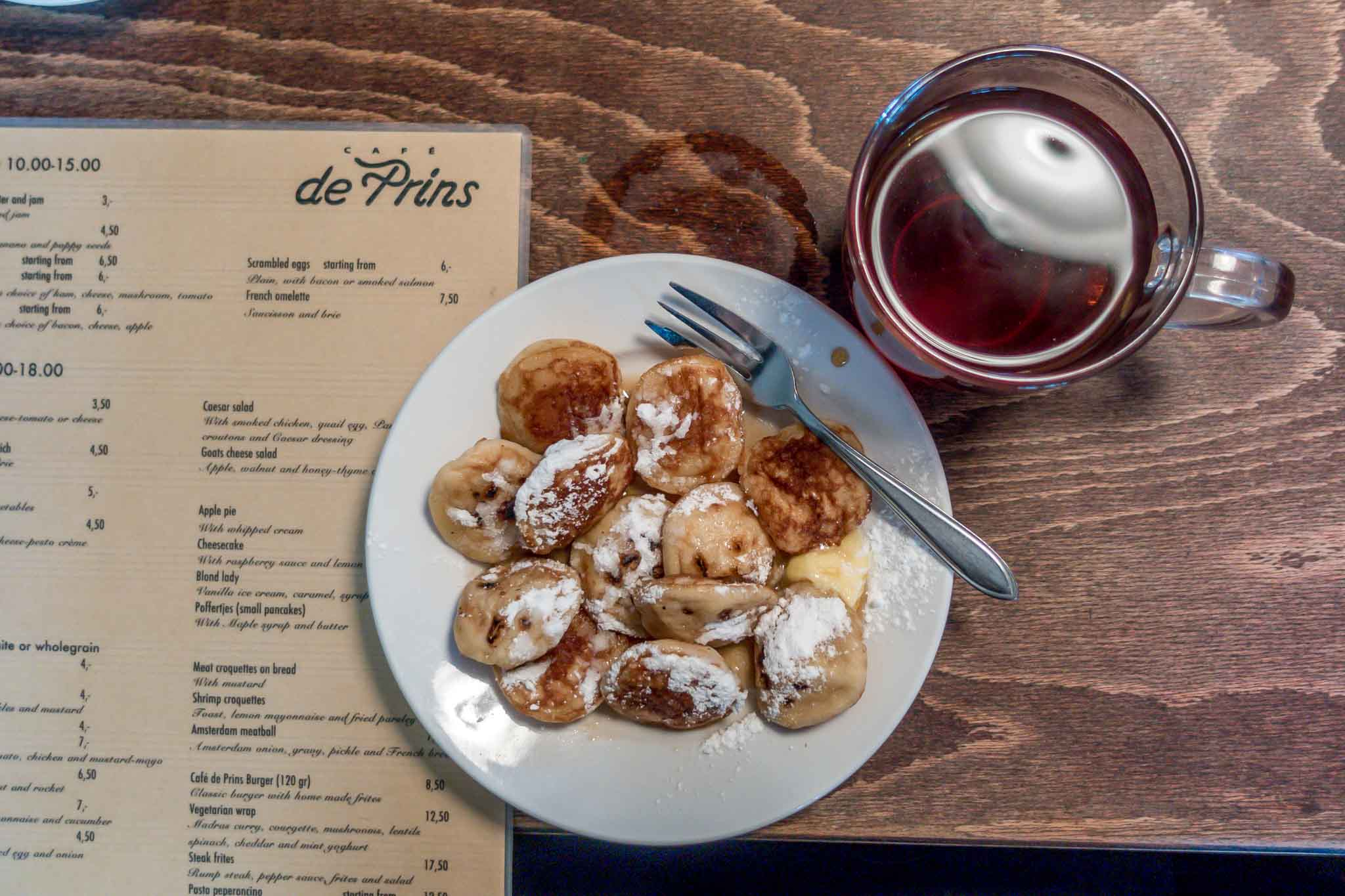Small Dutch pancakes on a plate with a cup of tea and a menu