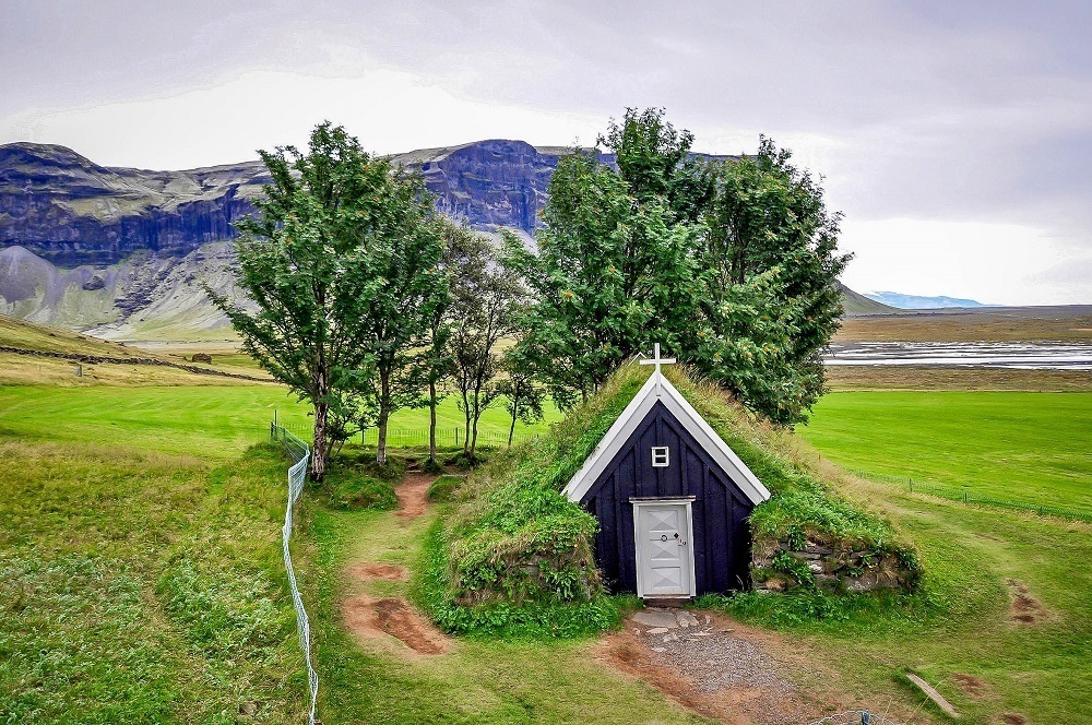 A green turf church in the Iceland countryside.