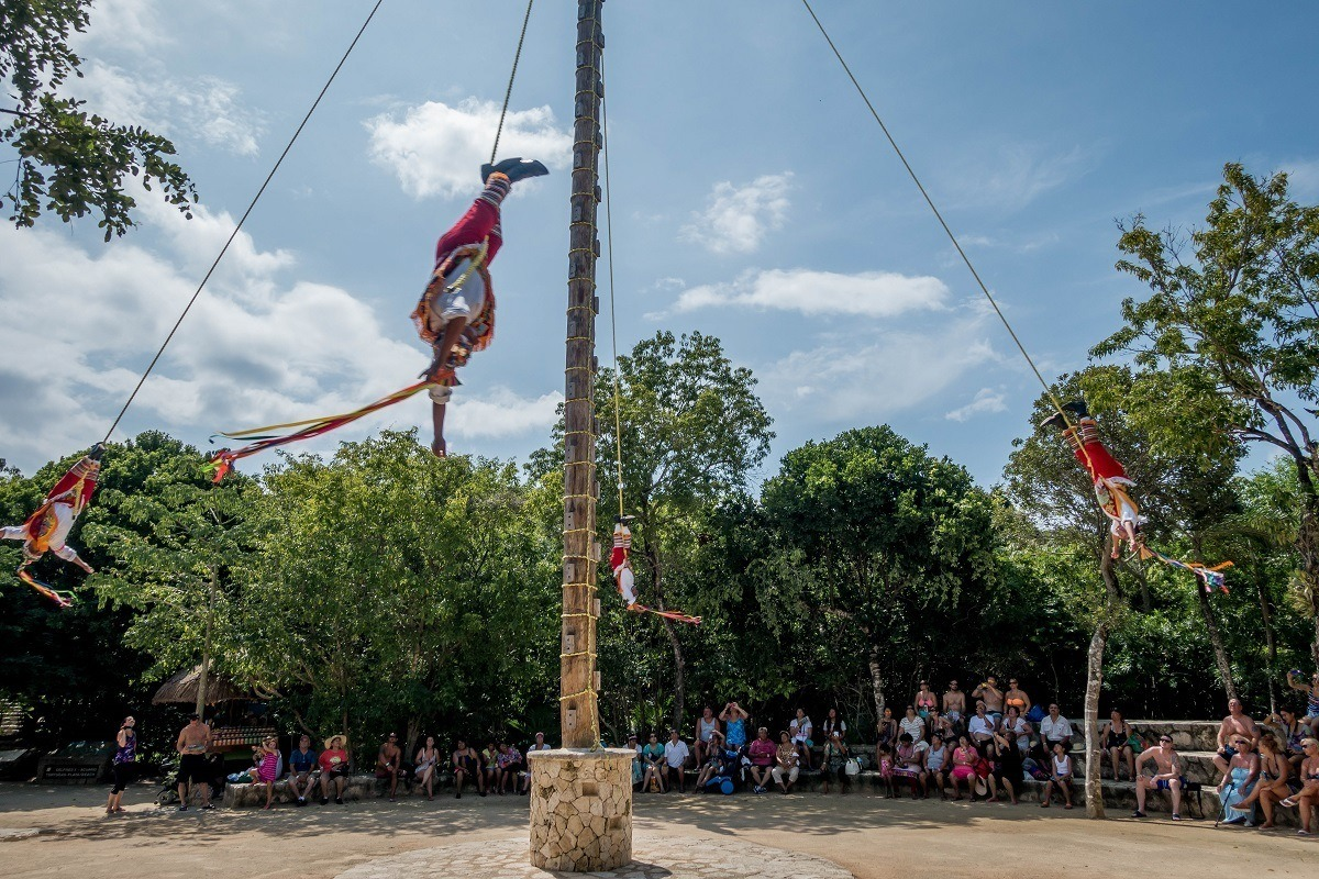 Men hanging and spinning on ropes, Papantla flyers perform a ritual at Xcaret Mexico Riviera Maya.