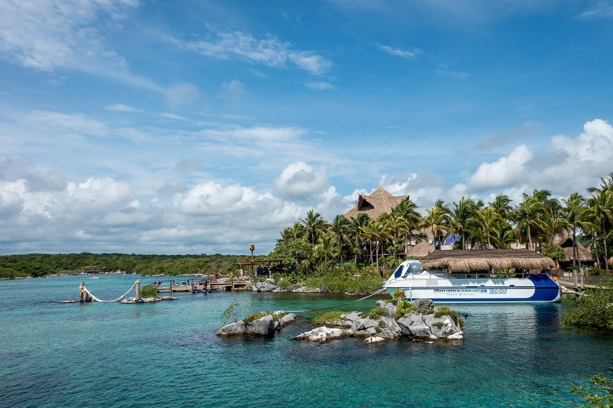 Ocean scene with a boat, palm trees, and rocks at Xel-Ha park