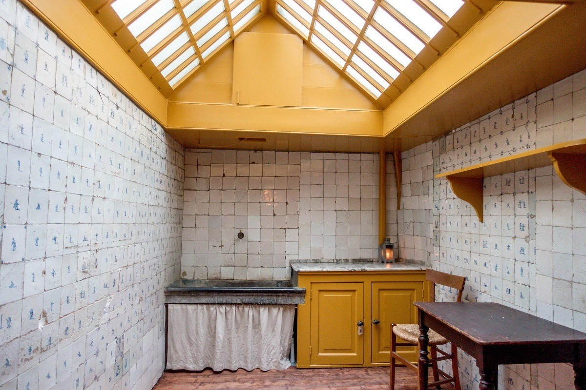 Kitchen with Delft blue tiles and yellow woodwork