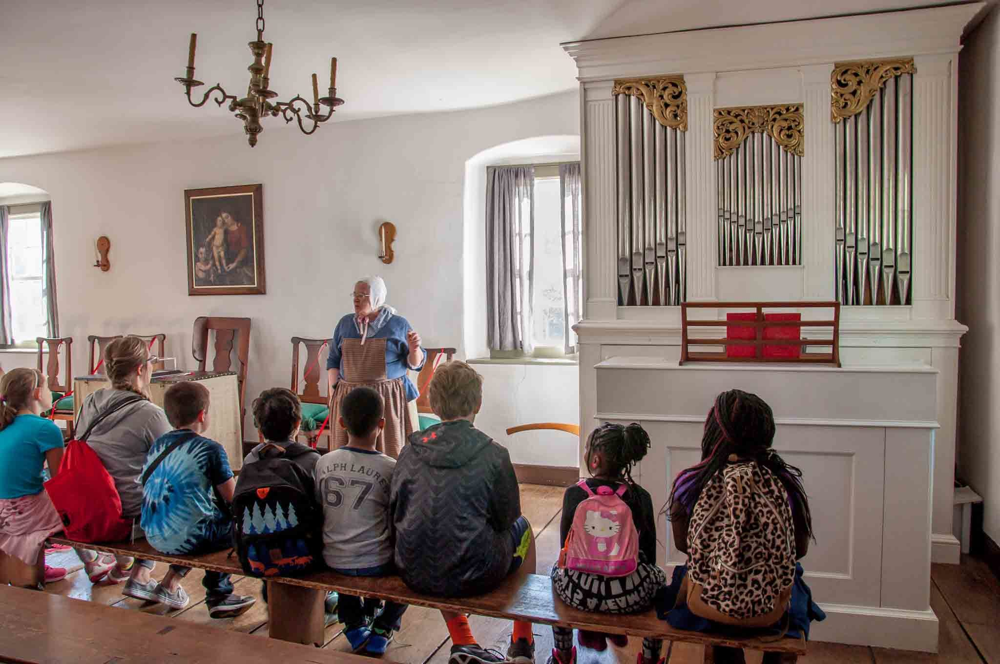 Group of children listening to a lecture in the chapel by an organ