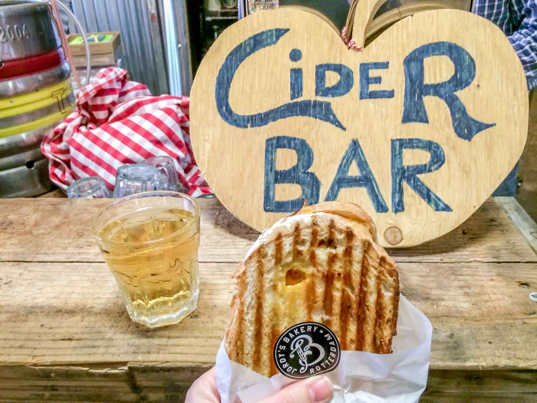 """""""Cider Bar"""" sign, sandwich, and drink on a table at the Fenix Food Factory, a Rotterdam must see"""