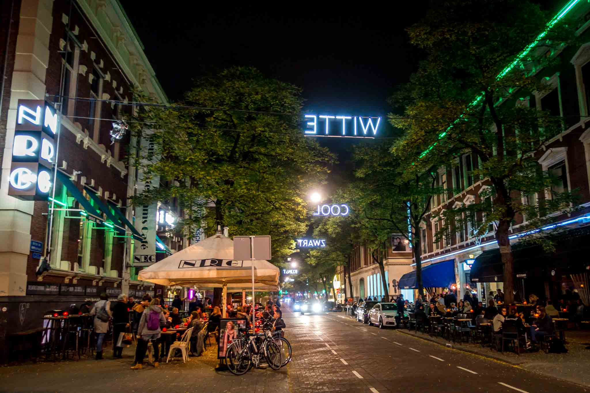 Rotterdam's colorful Witte de With Street with people at sidewalk cafes at night