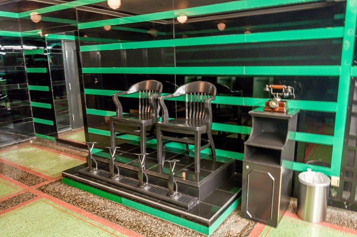 Shoe shine chairs in the famous green and black tiled men's bathroom