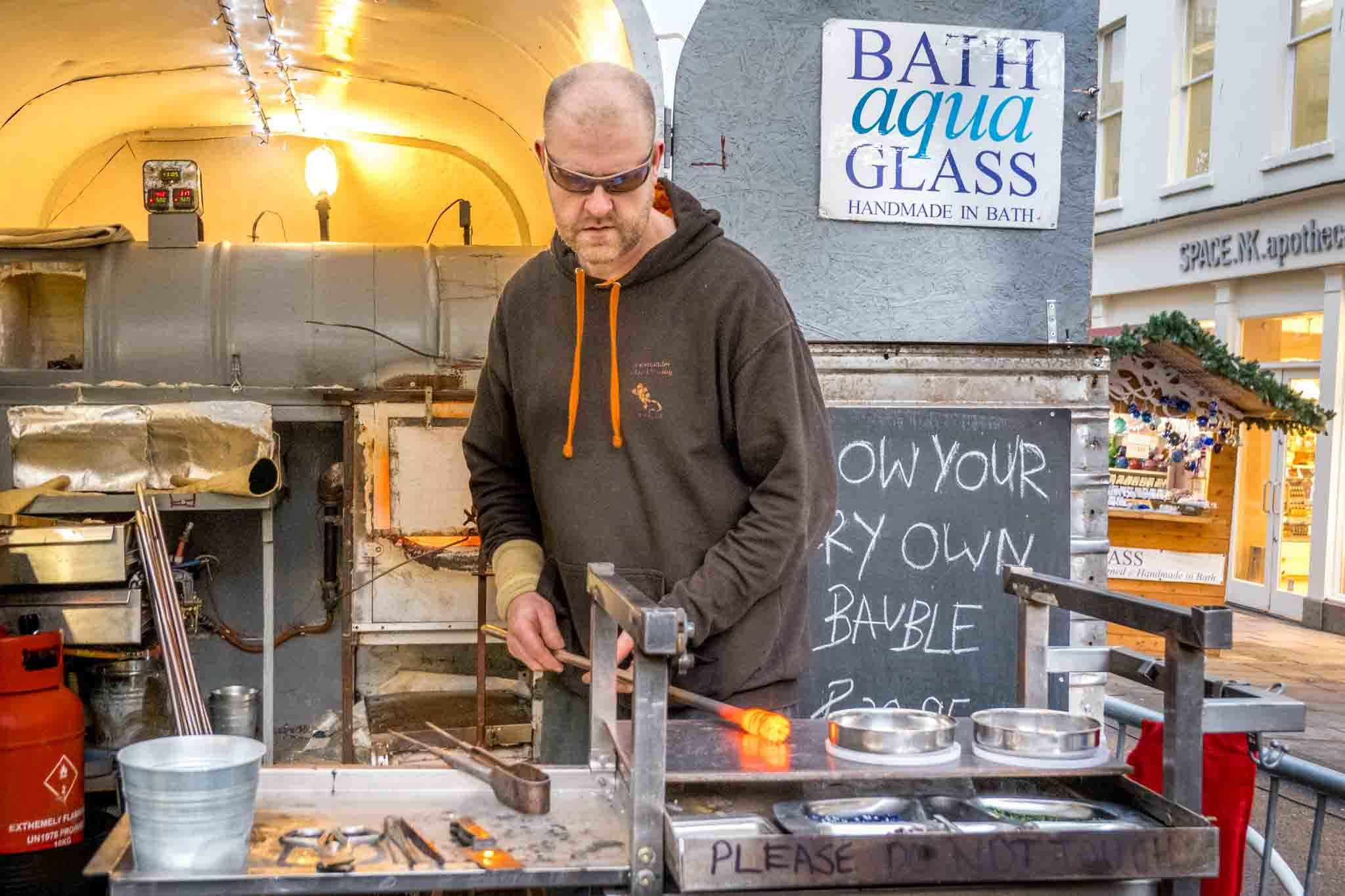 Man working on a blown glass creation at a mobile studio in the streets of Bath UK