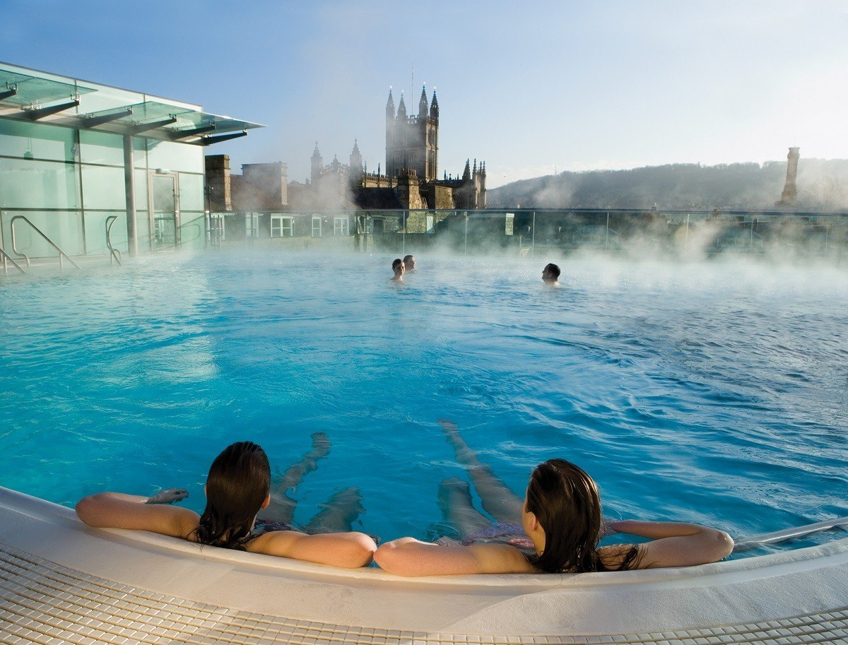 Bathers in the rooftop pool at the Thermae Spa with the Bath Abbey