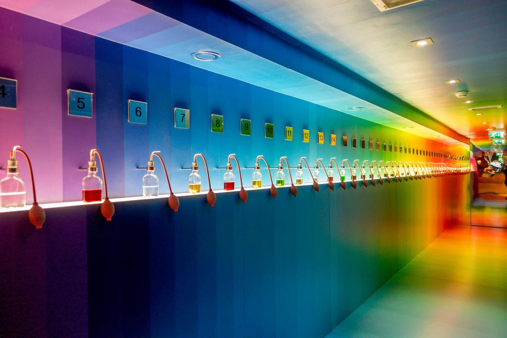 Rainbow colored exhibit with jars of colored liquid at House of Bols