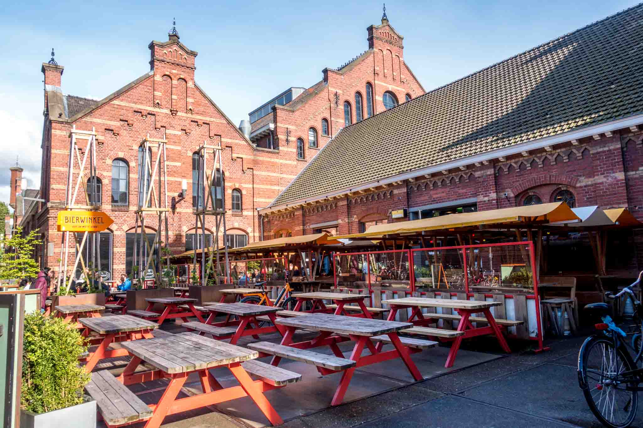 Troost Brewery outdoor seating and the red brick buildings of Westergasfabriek, one of the best spots in Amsterdam to enjoy the park and cafes