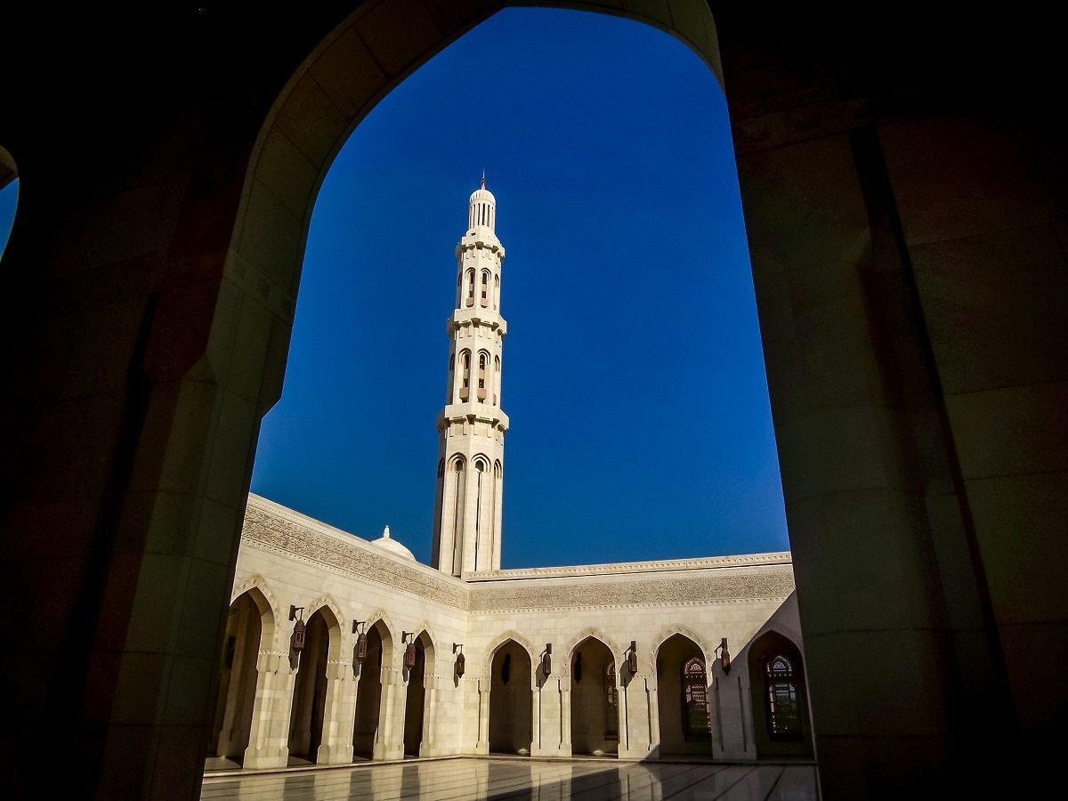 Minaret of the Grand Mosque in Muscat seen through an arch