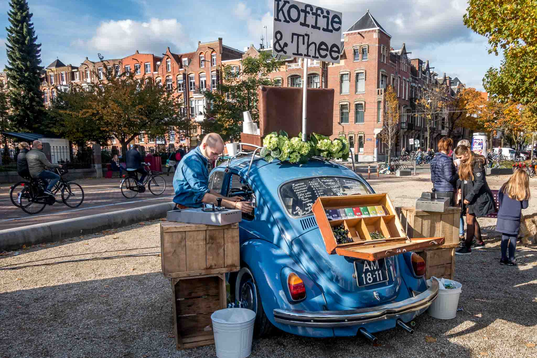 Man serving coffee from a VW bug at the Museum market in Amsterdam
