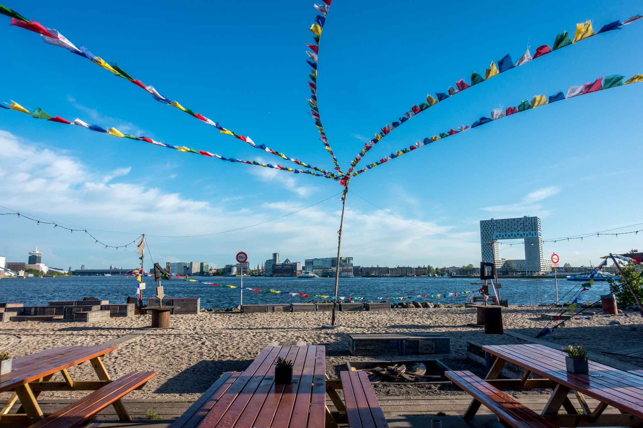 Picnic tables on a beach with flags flying overhead