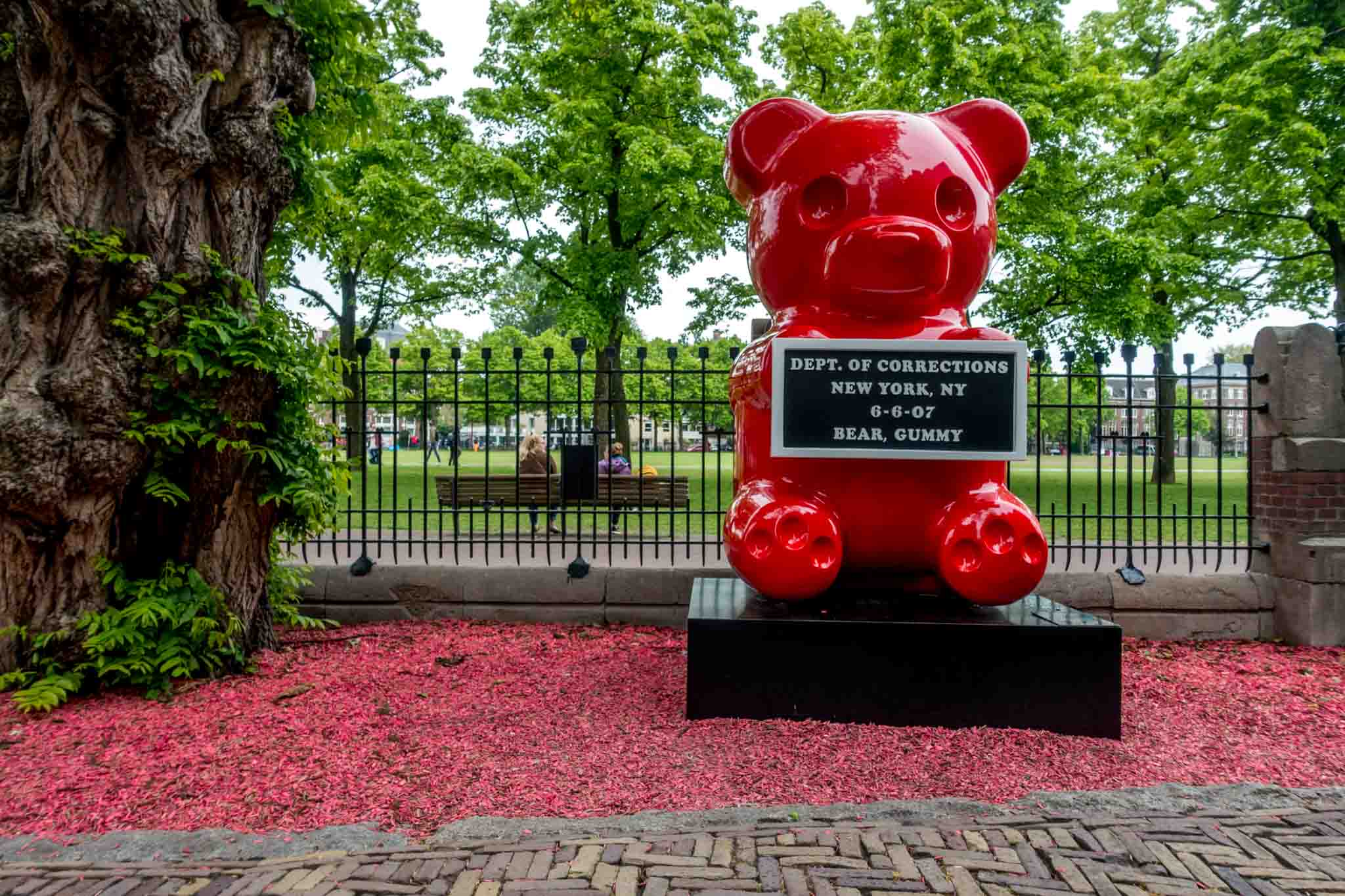Red gummy bear statue holding a mug shot plaque in the garden of the MOCO Museum in Amsterdam Netherlands.