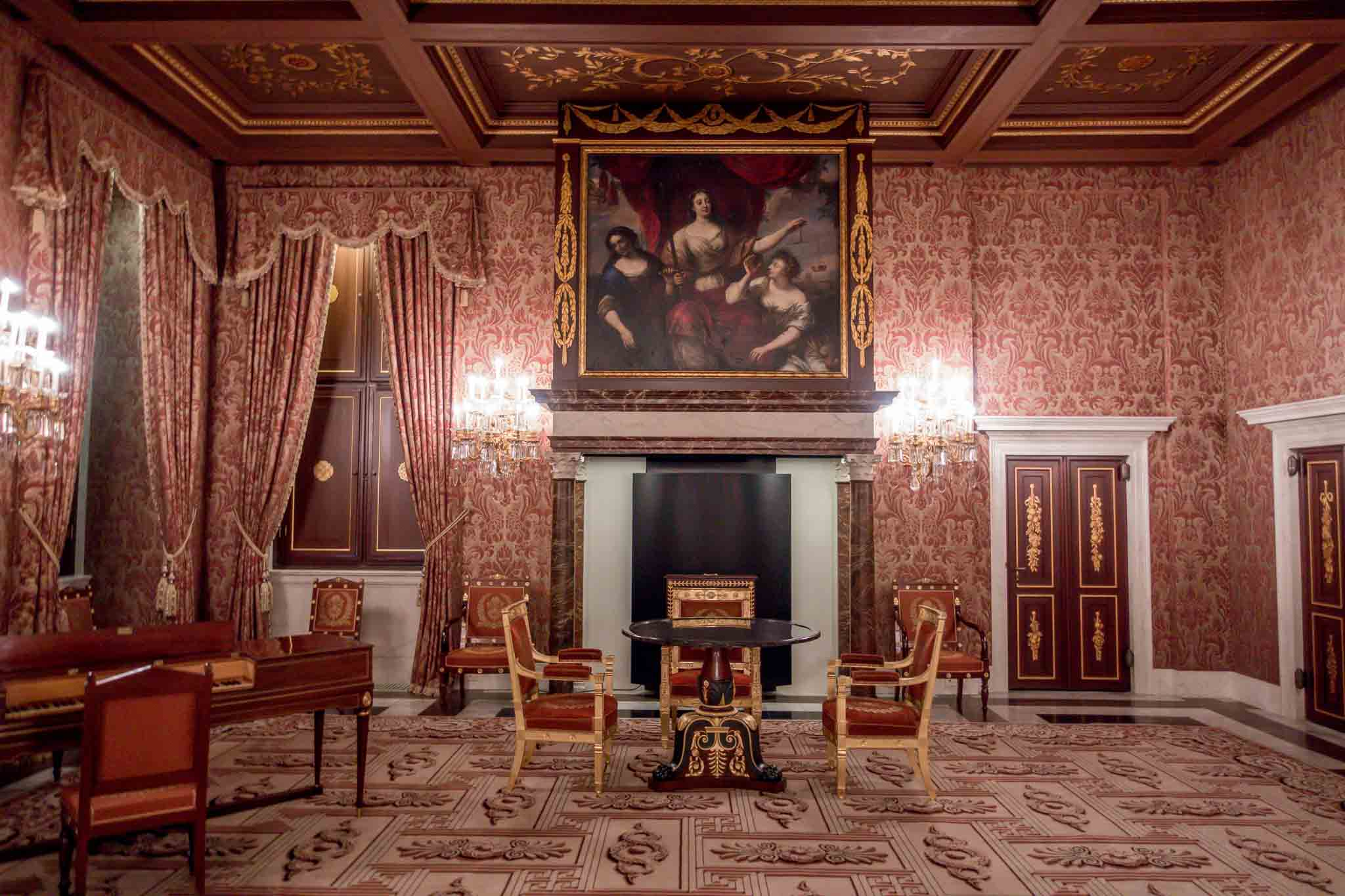 Room with red curtains, wallpaper, and furniture in The Royal Palace